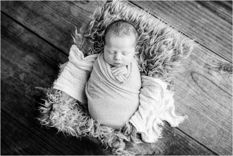 Black and white portrait newborn sleeping in basket with fur cloth by Moscow Baby Photographer Crystal Satriano