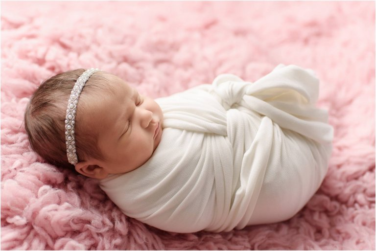 Baby girl posed in white wrap on big fuzzy blanket by Crystal Satriano