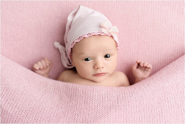 Baby girl covered in pink blanket with sleep hat by Scranton Newborn Photographer Crystal Satriano