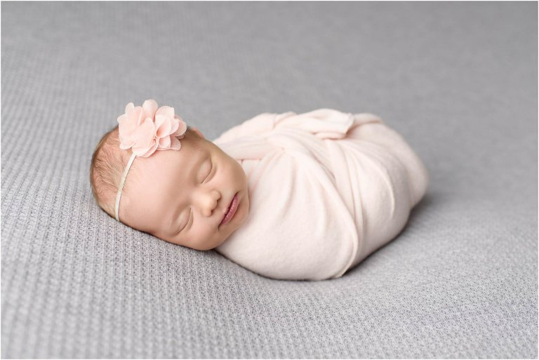 Scranton Newborn Photographer Crystal Satriano takes picture of baby girl in pink with flower headband