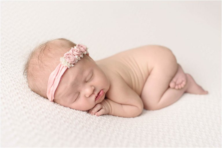 Baby girl laying on belly with pink headband captured by Scranton PA newborn photographer Crystal Satriano