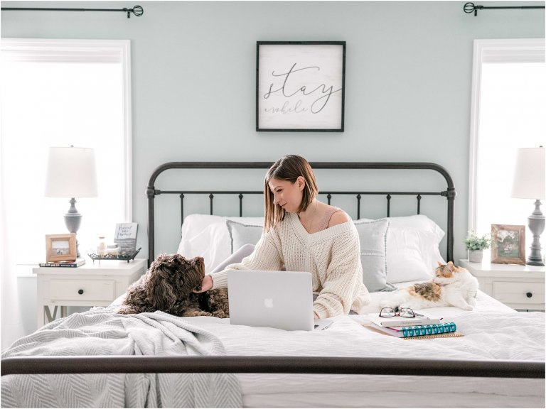 woman on bed in farmhouse bedroom with animals and working from home