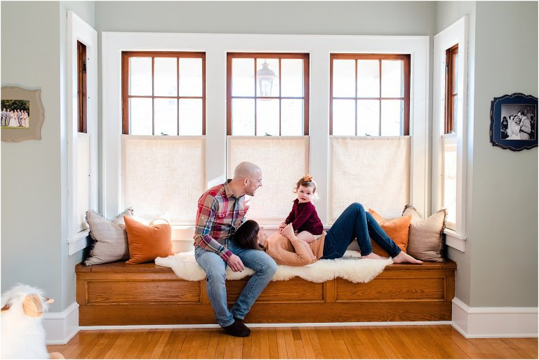Family sitting in a window bench seat in blue room of old house.