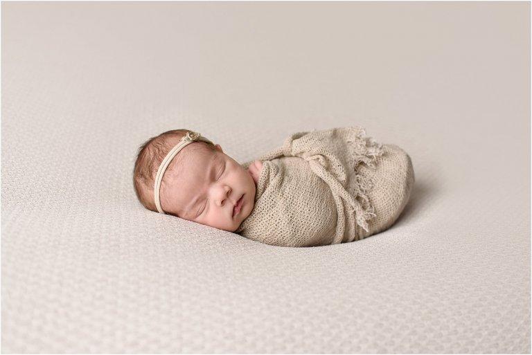 Newborn girl wrapped in beige on a beige backdrop for portrait in a Scranton newborn photography studio.