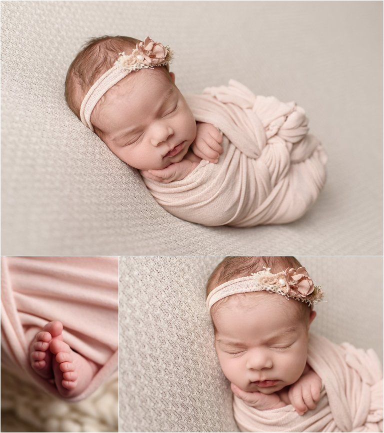 Newborn baby girl wrapped in pink with pink headband on beige backdrop in a Scranton newborn photography studio.